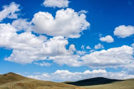fluffy clouds over green hills