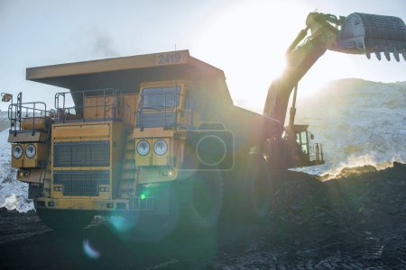 Big yellow dump truck and excavator in coal mine at sunrise