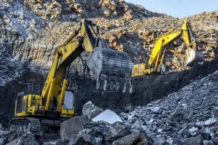 Big yellow excavators in coal mine at sunny day