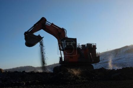 Big orange excavator in coal mine at sunny day