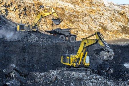 Big yellow excavators and orange truck in coal mine at sunny day