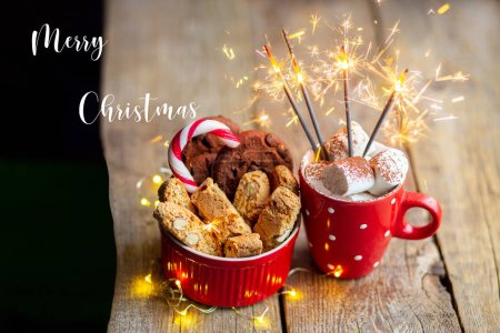 Photo for Christmas cookies on a wooden table with cocoa and marshmallows. Christmas candy with a toy on the Christmas tree. Hot drink with chocolate chip cookies. Sparkler in a cup. Christmas 2020. Sparkler - Royalty Free Image
