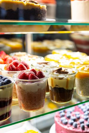 Photo for On the window are desserts in glasses with strawberries and berries. Snickers dessert in a glass. Showcase with cheesecake, pastries, macaroons in the store. Sweets in the fridge for the holiday. Cake - Royalty Free Image