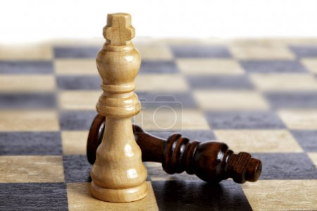 Close up checkmate wooden pieces on chessboard