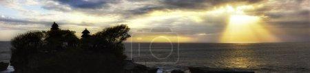 Foto de Hermosa fotografía de tierra sobre el mar y el templo. El sol brilla entre las nubes creando reflejos en la superficie del océano. - Imagen libre de derechos