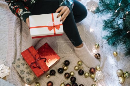 Photo for Photo can be use in websites, Christmas cards, blogs and posters. Girl in winter sweater holding gift box while sitting on blanket with Christmas presents and ornaments, with copy space, close-up. - Royalty Free Image