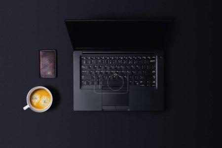 Schwarzer Arbeitstisch. Arbeitsplatz auf schwarzem Tisch mit Kaffee und Geldbörse.