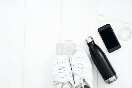 Photo for Fitness tracking concept. Using smartwatches and smartphones to track fitness activities. Running shoes flat lay view. - Royalty Free Image