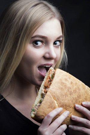 Photo pour Portrait dans une veine sombre d'une belle jeune femme mordant un délicieux sandwich - image libre de droit