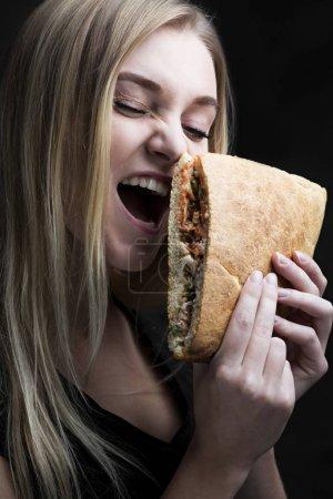 Photo pour Portrait charismatique d'une jeune femme avec une restauration rapide savoureuse d'une manière noire - image libre de droit
