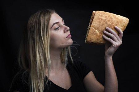 Photo pour Portrait de mode d'une femme dans une touche noire avec un délicieux sandwich dans les mains - image libre de droit
