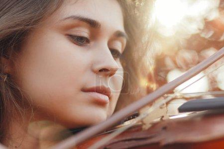 Photo pour Visage d'une belle femme avec du violon sous son menton, fille romantique engagée dans l'art, interprétation de la nature automnale, concept de passe-temps et musique - image libre de droit