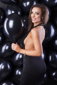 Beautiful and elegant woman with balloons and champagne ready for New Years Eve!