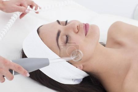 Photo for Beautician is doing a facial treatment to her patient. - Royalty Free Image