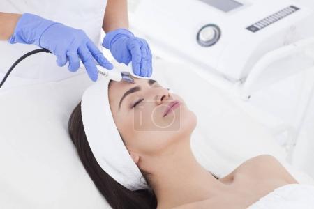Photo pour Esthéticienne fait un soin du visage à sa patiente . - image libre de droit
