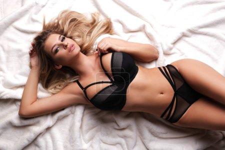 Photo pour Sexy, beautiful model in lingerie is lying on white fur. - image libre de droit