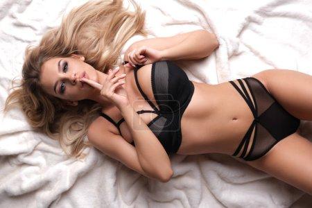 Photo pour Sexy, beautiful model lying on white fur. - image libre de droit