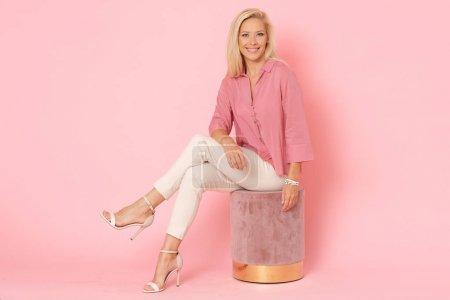 Photo pour Élégante blonde adulte avec un sourire charmant assise sur un pouf en velours rose . - image libre de droit