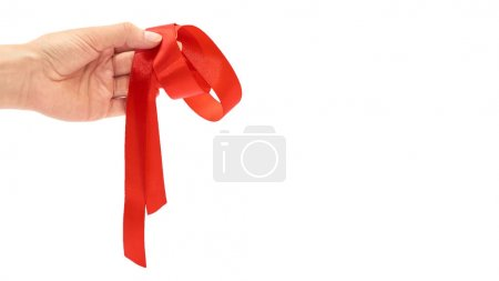 Female hand holds red gift wrapping tape. Isolated on white background. copy space, template