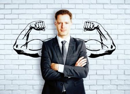 Photo for Confident businessman with drawn muscly hands on brick background. Strength concept - Royalty Free Image