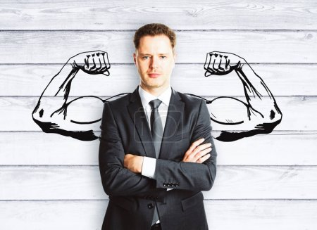 Photo for Confident businessman with drawn muscly hands on wooden background. Hero concept - Royalty Free Image