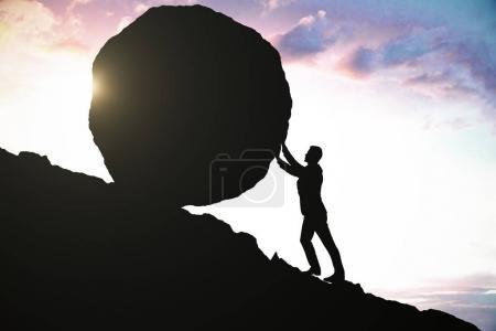Photo pour Vue latérale de la silhouette masculine poussant énorme rocher vers le haut. Beau fond de ciel. Concept de détermination - image libre de droit