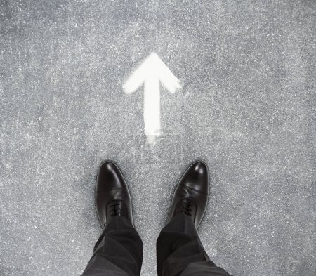 businessmen feet on concrete floor with drawn arrow