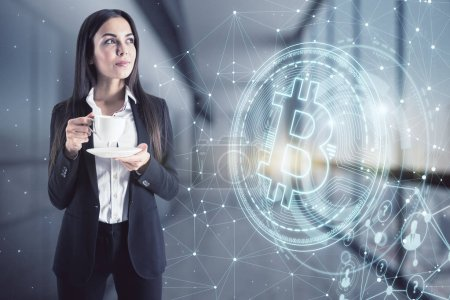 Photo for Finance and cryptocurrency concept. Portrait of attractive young european businesswoman drinking coffee with glowing bitcoin hologram on blurry office interior. Multiexposure - Royalty Free Image
