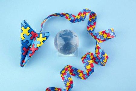 Foto de Concienciación del autismo día o mes. Plano de papel en estilo origami con cintas de rompecabezas de conciencia de autismo sobre fondo azul. Vista superior - Imagen libre de derechos