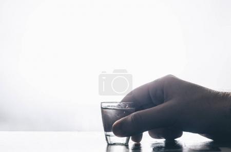 Photo pour Main d'homme tenant un verre avec de la vodka - image libre de droit