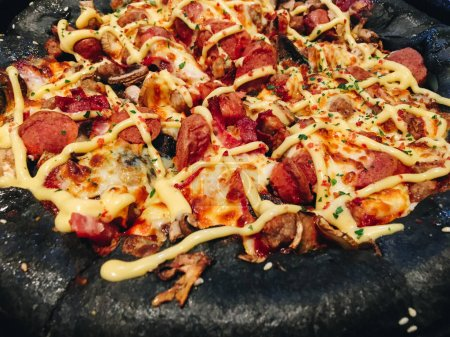 Photo for Unusual pizza with black dough, sausages and cheese. - Royalty Free Image