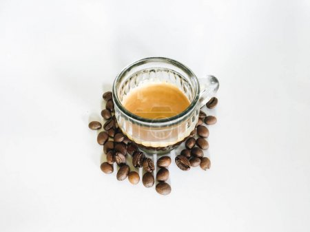 Photo for Hot coffee served in glass mug with scattered coffee beans on table - Royalty Free Image