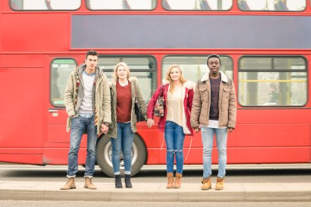 Group of fashion friends crossing the road with typical red bus behind - Autumn winter concept of social life with young people hanging out together - Neutral color tones with focus in guys and girls