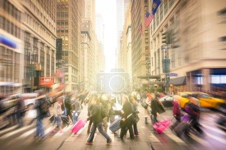Photo pour Les gens marchent sur la 7 ème av. et West 34 e carrefour à Manhattan avant le coucher du soleil - Rues bondées de New York à l'heure de pointe dans la zone d'affaires urbaine - Composition floue radiale avec accent sur le fond - image libre de droit