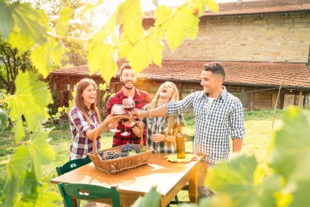 Happy friends having fun drinking wine at winery vineyard - Friendship concept with young people enjoying harvest time together at farmhouse - Warm filter with enhance sun flare halo - Leaves in frame