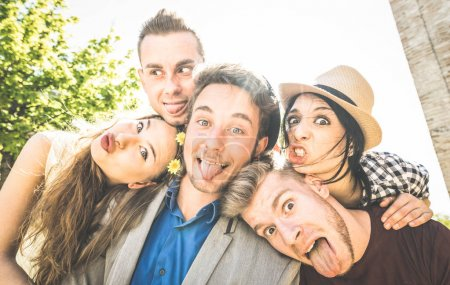 Photo for Group of best friends taking selfie outdoor with back lighting - Happy concept with young people having fun together - Cheer and friendship at city tour - Retro vintage filter with focus on middle guy - Royalty Free Image