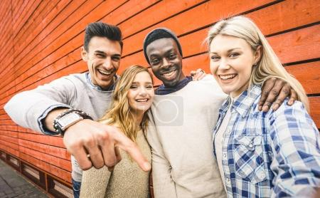 Photo for Happy multiracial friends group taking selfie with mobile smart phone - Young hipster people addicted by smartphone on social network community - Lifestyle technology concept on vivid contrast filter - Royalty Free Image