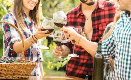 Photo for Young friends having fun outdoor clinking red wine glasses - Happy people eating grape and drinking at harvest time in farmhouse vineyard winery - Youth friendship concept with shallow depth of field - Royalty Free Image