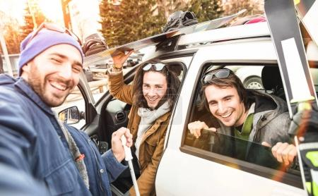 Photo for Best friends having fun taking selfie at car for ski and snowboard on mountain trip - Friendship hangout concept with young people loving winter sports travel - Vintage desaturated contrast filter - Royalty Free Image