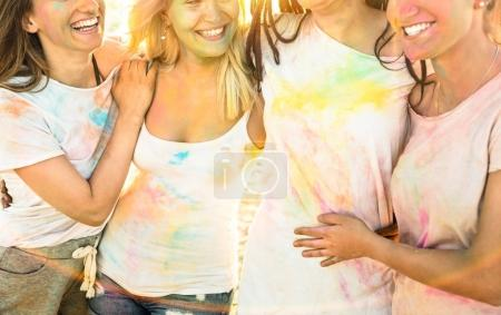 Happy girlfriends having fun at beach party on holi festival summer vacation - Young women friends together with genuine carefree mood - Youth and friendship concept with multi colored playful people