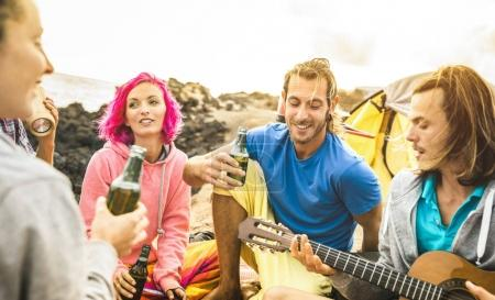 Hipster friends having fun together at beach camping party - Friendship travel concept with young people travelers playing guitar and drinking bottled beer at summer surf camp - Warm bright filter