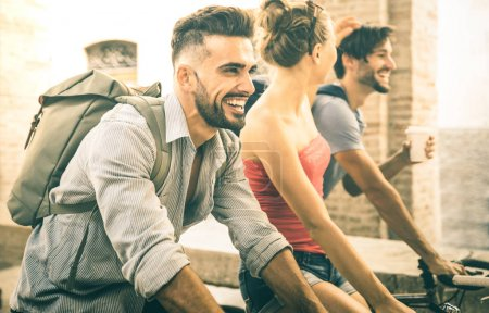Happy multicultural friends having fun riding bicycle in city old town - Friendship concept with young people students biking together to university college campus - Bright vintage retro filter