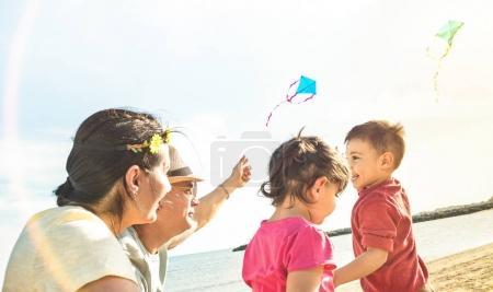 Photo pour Famille heureuse avec des parents et des enfants jouant ensemble avec cerf-volant lors de vacances à la plage - Concept de joie d'été avec des gens de race mixte ayant un pur plaisir authentique ensemble - Filtre rétro-éclairage au soleil chaud - image libre de droit