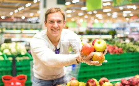 Young single man showing fruit and vegetables at shopping in grocery store supermarket - Modern healthy lifestyle concept concept with guy on bio food products purchase at vegetarian market place