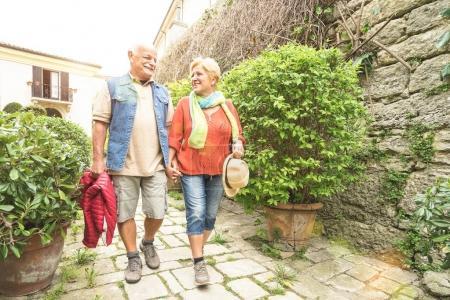 Photo pour Heureux couple de personnes âgées marchant main dans la main dans le château de la vieille ville de Saint-Marin - Concept actif de personnes âgées et de style de vie de voyage avec des personnes âgées à la retraite au voyage en Italie - Sunshine halo avec filtre solaire - image libre de droit