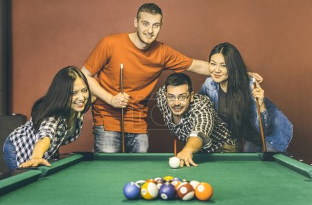 Young friends playing pool at billiard table saloon - Happy friendship concept with fashion people having fun together and sharing time at snooker gameroom - Warm vintage retro contrast filter
