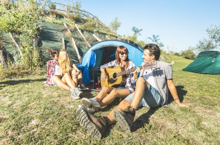 Friends group having fun outdoor cheering at picnic camp with vintage guitar - Young people enjoying summer time together at countryside party - Youth travel friendship concept - Warm bright filter