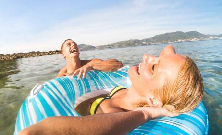 Young couple vacationer having genuine fun on tropical Phuket beach in Thailand - Snorkel tour in exotic scenario - Active youth love and travel concept around world - Bright warm color filter tones