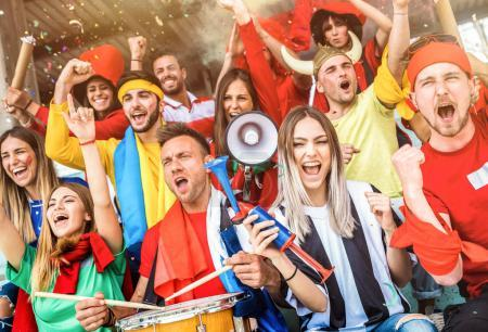 Football supporter fans friends cheering and watching soccer cup match at intenational stadium - Young people group with multicolored t-shirts having excited fun on sport world championship concept