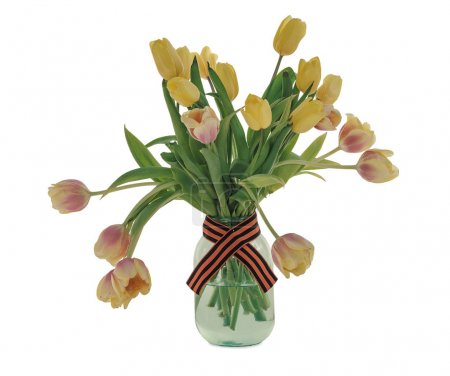 A bouquet of yellow tulips in a glass jar with a St. George ribbon. White isolated background.